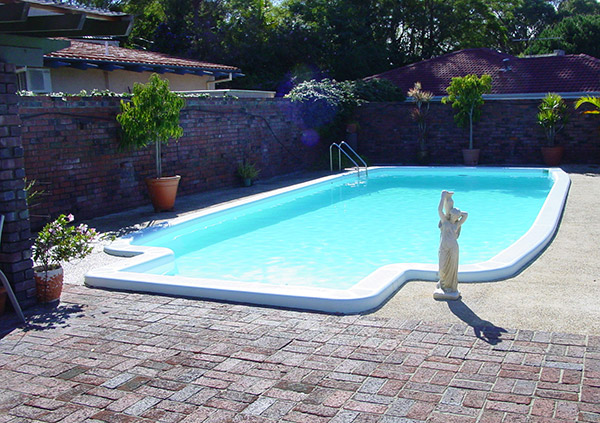 A fibreglass swimming pool with brick paving and plants lining the edge