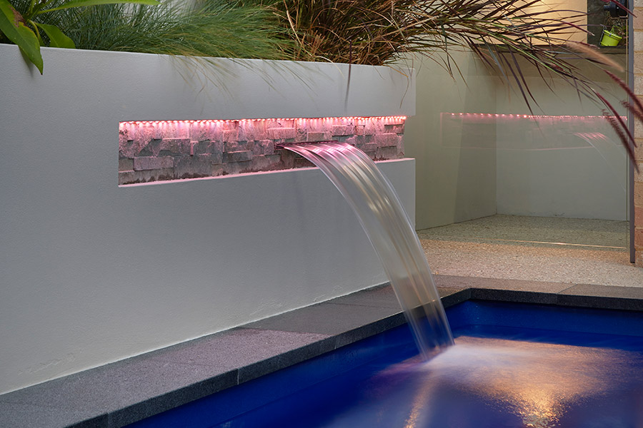 Backyard fibreglass swimming pool with water feature